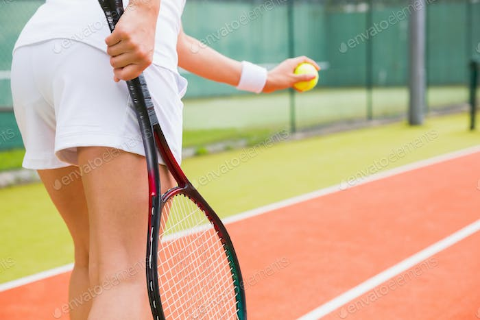 Tennis player getting ready to serve on a sunny day
