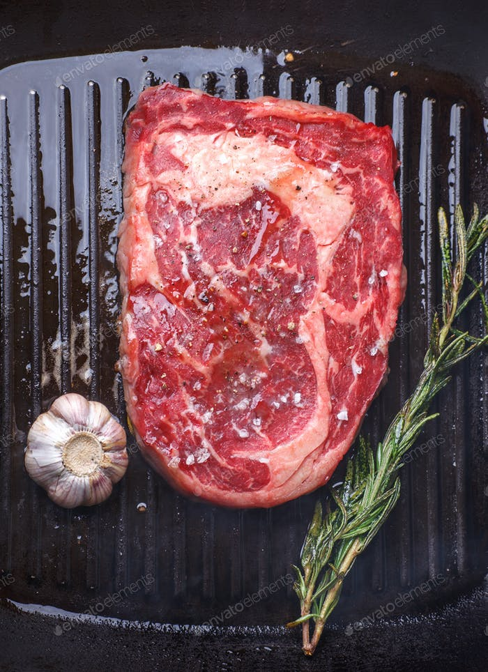 marble beef steak roasting in grill pan with garlic and rosemary