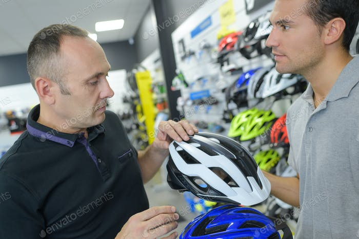 bike shop assistant helps customer to choose helmet