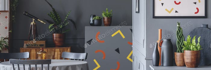 Dark grey room interior with dining table with chairs and cupboa