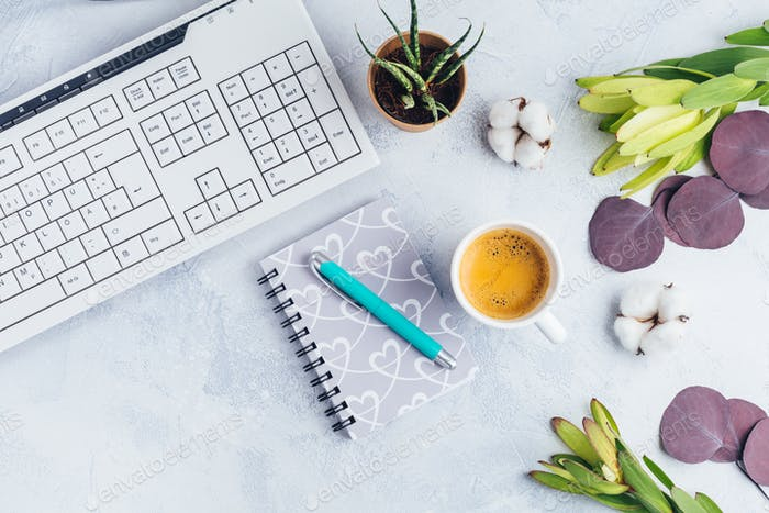 Cup of coffee, with communication device with and writing tools. Flat lay home business desk