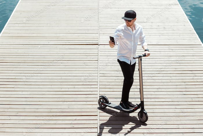 Modern man dressed white shirt and black pants using his phone while standing at a wooden pier with