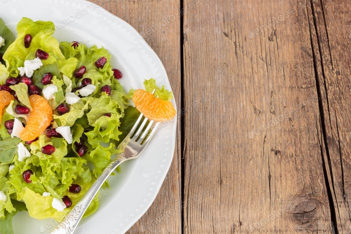 Healthy salad with pomegranate and mandarins