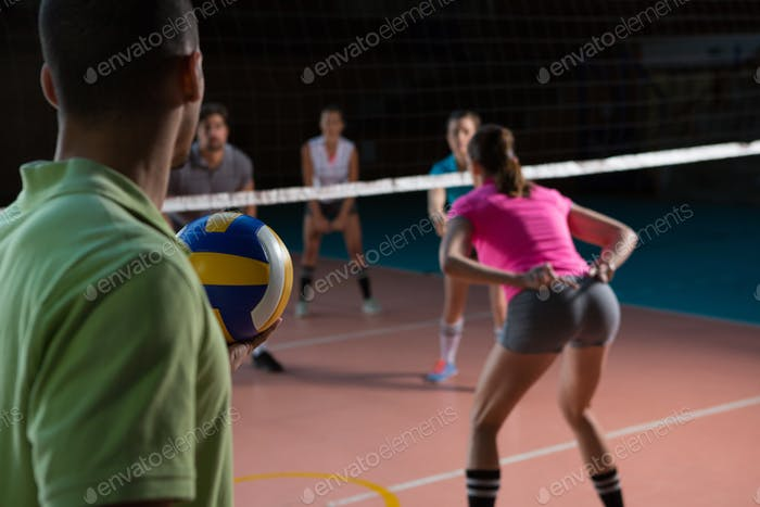 Male player playing volleyball with teammates