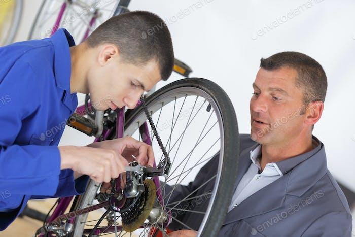 teacher showing aprentice how to fix a bike