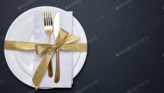 Gold cutlery on white set of dishes, black background, top view