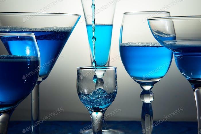 Viele Gläser mit blauem Champagner oder Cocktail.