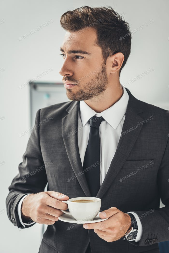 handsome young businessman in stylish suit with cup of coffee