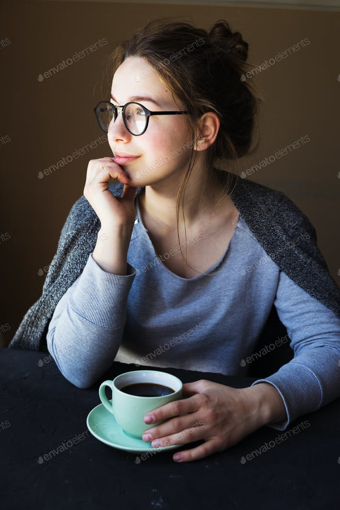 Young woman sitting in diner with cup of coffee