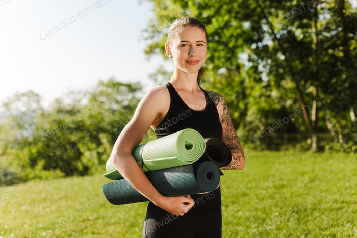 Portrait of smiling lady in black sporty top and leggings standing with yoga mats in hands