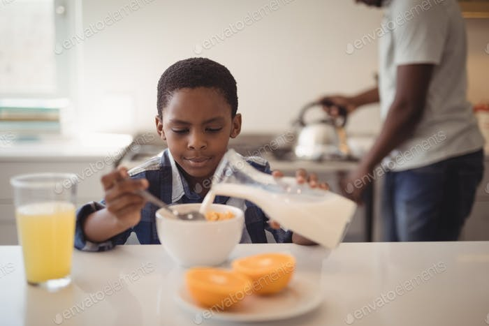 Boy pouring milk into breakfast cereals bowl in kitchen