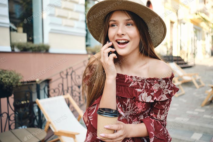 Young stylish girl in dress and straw hat happily talking on cellphone on cozy city street
