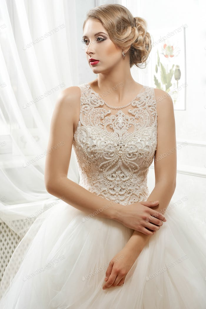 Young beautiful bride, woman in long white wedding dress on whit