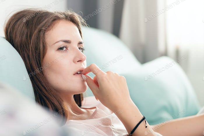 Young woman lying on couch and thinking about something at home