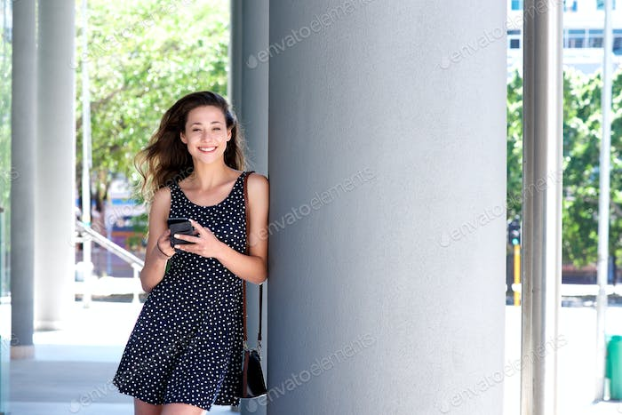 smiling woman in dress standing outside with mobile phone