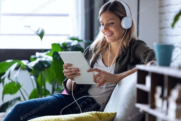 pretty young woman listening to music with headphones and her digital tablet  on sofa at home.