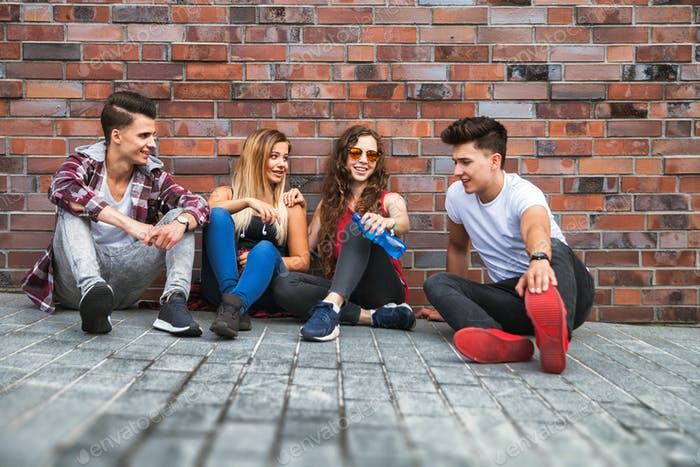 Group of young friends sitting on street and talking