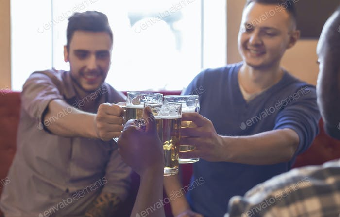 Happy mates clinking glasses with beer together