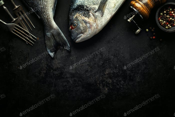 Dorado fish with ingredients on dark