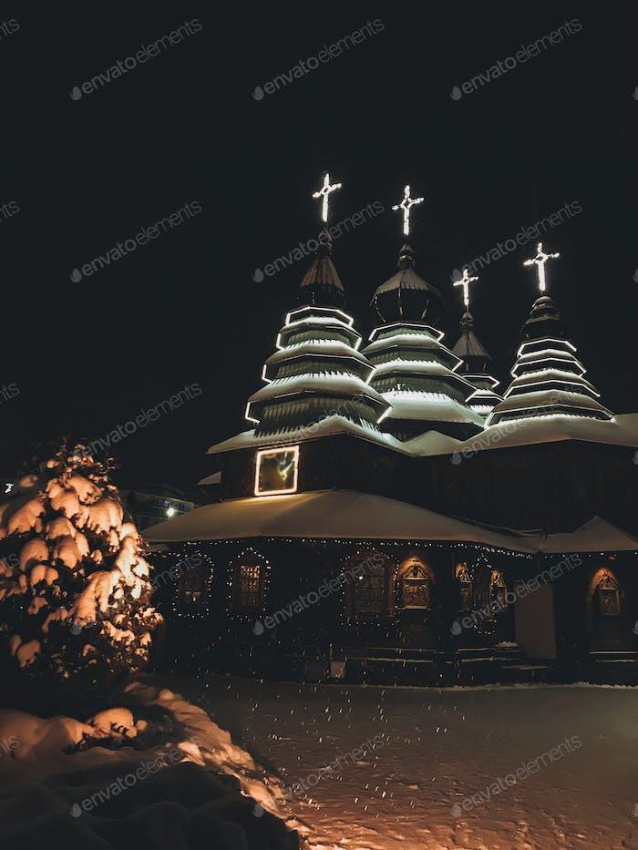 Christmas evening near christian church in snowy weather