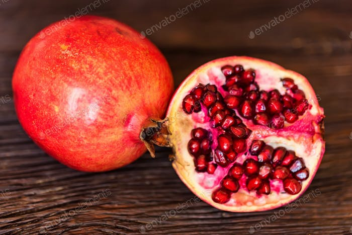 Ripe pomegranate fruits on wooden background