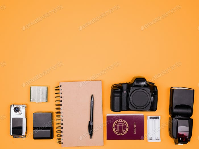 Flatlay accesories of a travel blogger on pastel orange background
