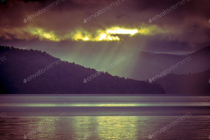 Sunrays falling through clouds over foggy mountain lake in vinta