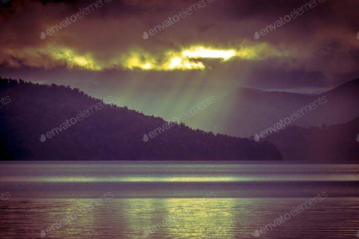 Sonnenstrahlen fallen durch Wolken über nebligen Bergsee in vinta