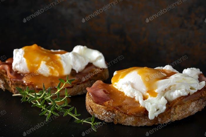 Homemade Benedict eggs on a dark slate