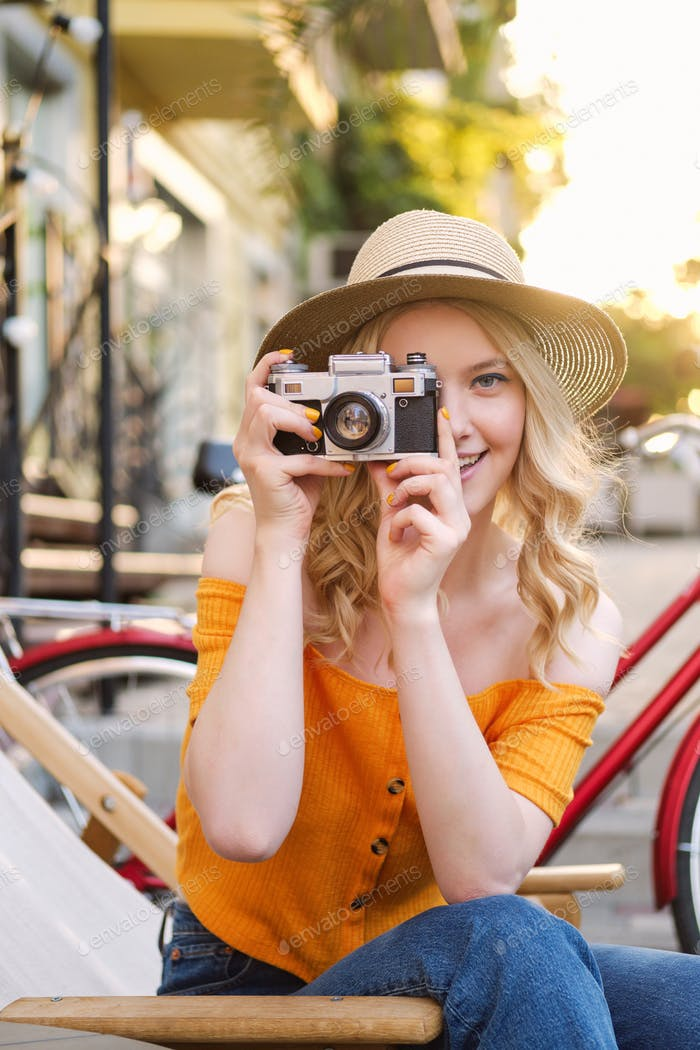 Pretty casual blond girl in hat dreamily taking photo on retro camera on deck chair in street cafe