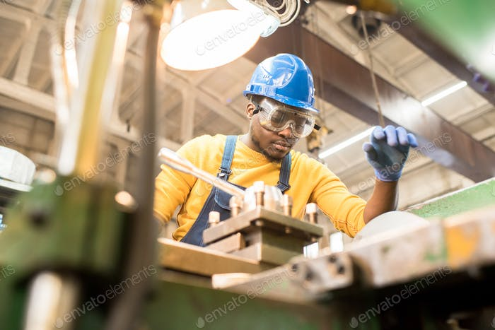 Serious worker repairing manufacturing machine