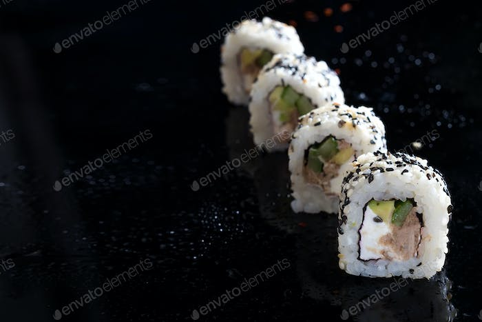 Sushi roll with fish, vegetables and cheese on black glass with reflection. Traditional japanese