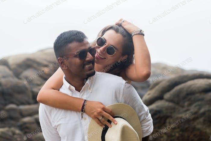 Porträt des liebevollen jungen Paares am Strand. Sie sind glücklich und lächeln.