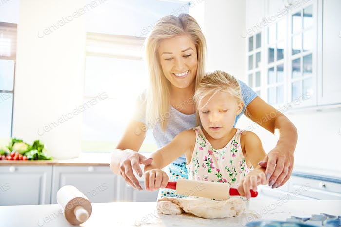 Cute little girl learning to roll out dough