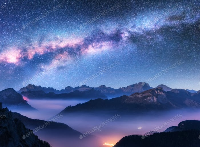Milky Way above mountains in fog at night in autumn
