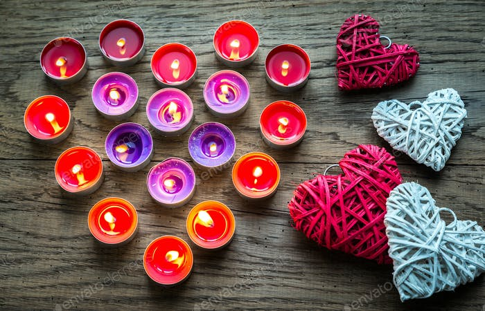 Burning candles with retro cane hearts