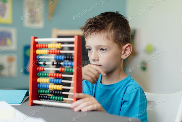 Thinking schoolboy learning maths with an abacus