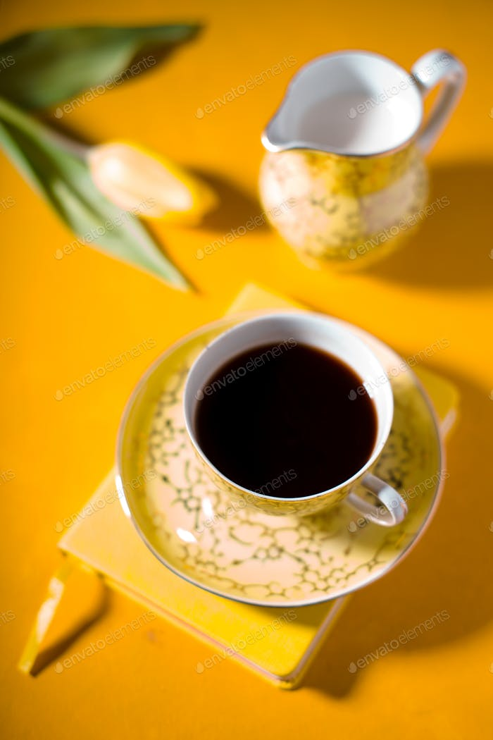 Cup with coffee, notebook, tulip on yellow background