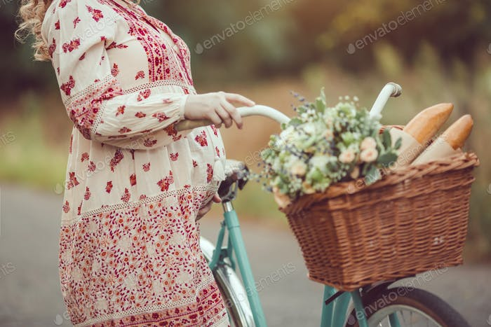 Pregnant belly against nature close-up. Woman retro French style with bicycle on a forest road