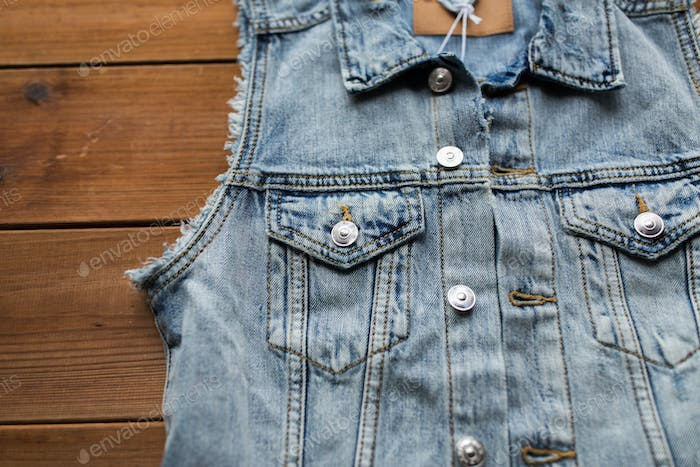 close up of denim vest or waistcoat on wood