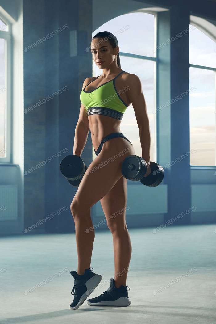 Athletic sporty woman posing with dumbbells