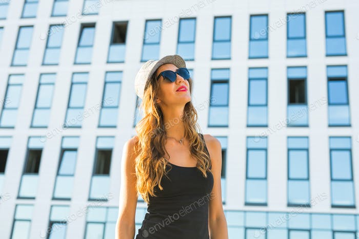 Sunny lifestyle fashion portrait of young stylish hipster woman walking on the street