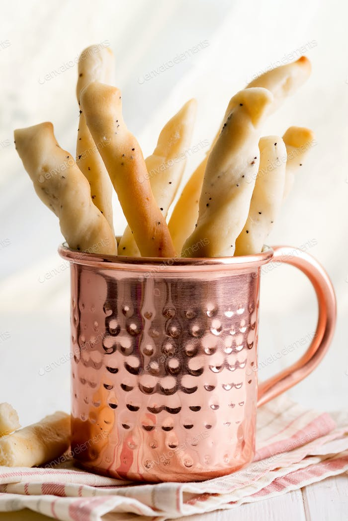 Italian traditional homemade bread sticks grissini in a copper cup on wooden table