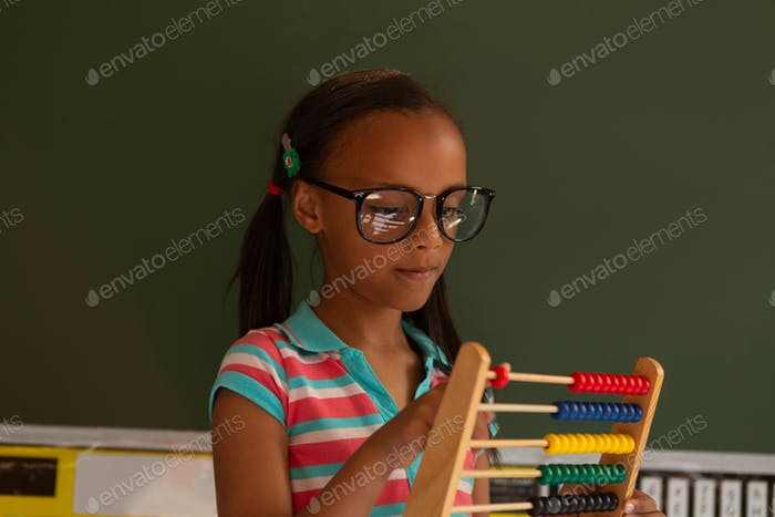 Cute mixed-race schoolgirl learning mathematics with abacus in the classroom