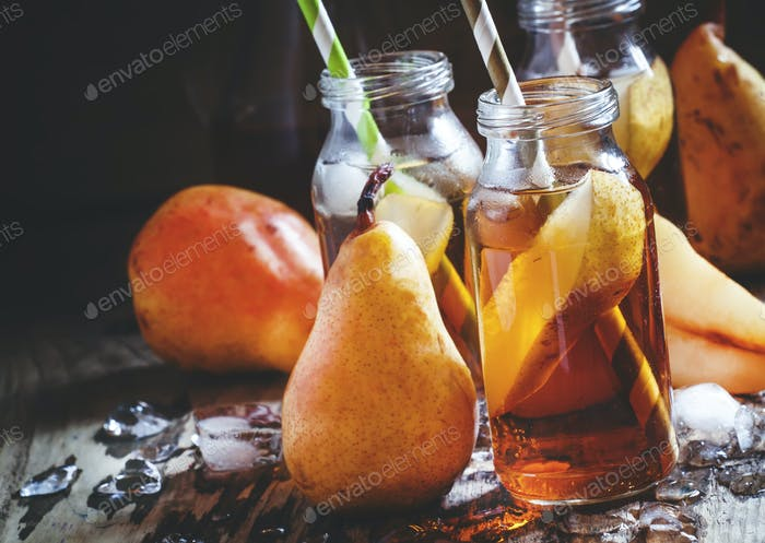Clarified pear juice with ice and slices of fruit in glass bottles with straws
