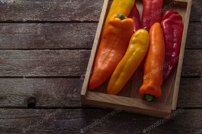 Ripe Colorful Peppers on Wooden background, copy space