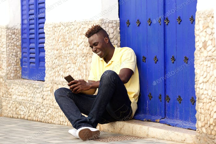 Stylish young african man sitting outside and using mobile phone