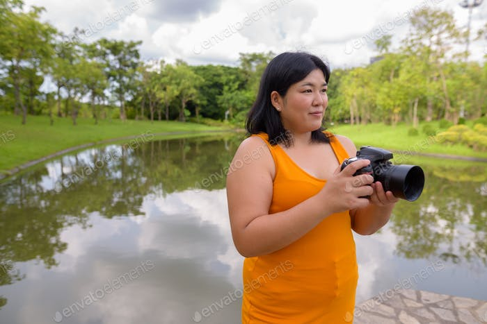 Beautiful overweight Asian woman photographer in park