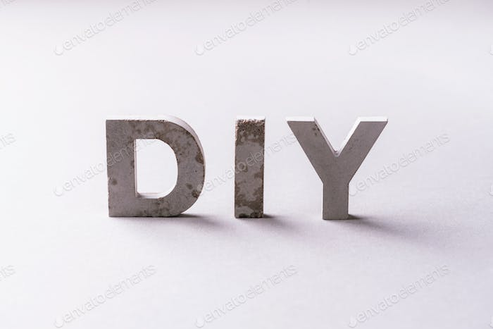 Word diy from cement letters on grey background. Do It Yourself abrreviation