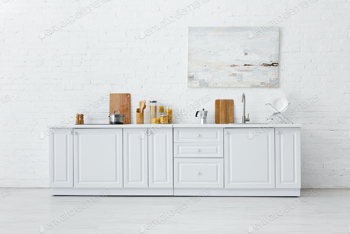 minimalistic white kitchen interior with kitchenware and painting on brick wall